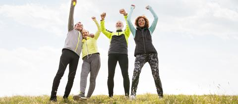 Zwei Mäner und zwei Frauen stehen in Sportkleidung auf einem Hügel