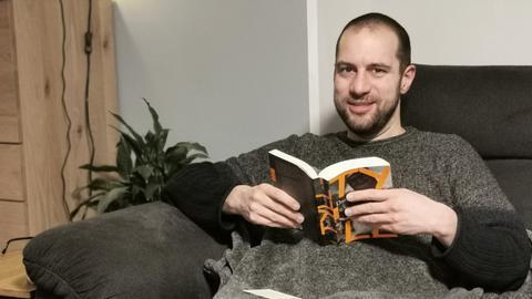 Jürgen Scholle liest auf dem Sofa