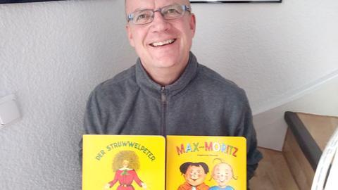 """Hermann Hillebrand mit dem Büchern """"Struwwelpeter"""" und """"Max und Moritz"""""""