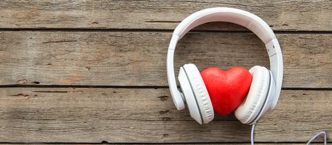 Ein Herz mit Kopfhörer liegt auf einer Holzplatte