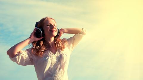 Frau hört genussvoll Musik mit Kopfhörern unter freiem Himmel