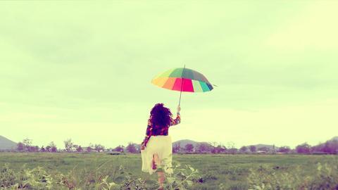 Tanzende Frau mit buntem Sonnenschirm auf grüner Wiese
