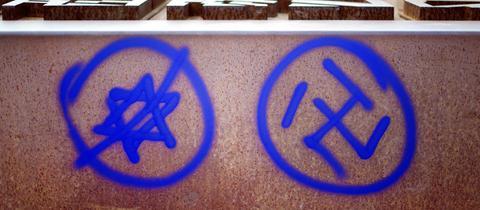Ein Hakenkreuz und ein durchgestrichener Davidstern sind an einer Gedenkstätte in Berlin zu sehen.