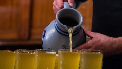 Apfelwein wird aus einem Bembel in Gläser geschüttet