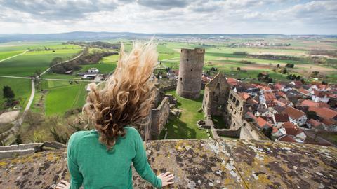 Die Haare einer Besucherin werden am 06.04.2015 in Münzenberg (Hessen) auf einem der beiden Türme der Burganlage vom starken Wind zerzaust. Unten sieht man einen Teil der Burg - ein Wahrzeichen der Wetterau - mit deren Bau im 12. Jahrhundert begonnen wurde.
