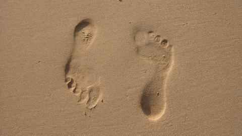 Zwei Abdrücke eines rechten Fußes im Sand