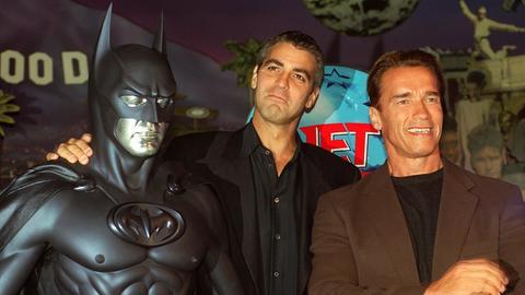 George Clooney, mit einer Batman-Figur, und Arnold Schwarzenegger