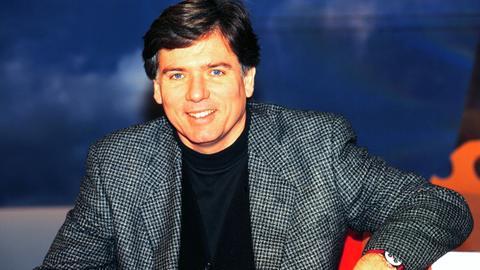 """Moderator Heinz Günter Heygen in seiner TV-Show """"8 und fertig los"""". In der Show mussten sich acht Kandidaten in Geschicklichkeitsspielen und Wissensfragen messen."""