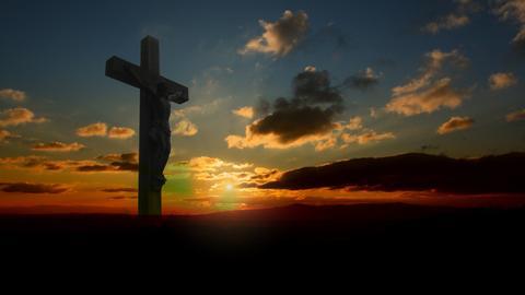 Geschnitzter Jesus am Kreuz auf einem Berggipfel im Sonnenuntergang