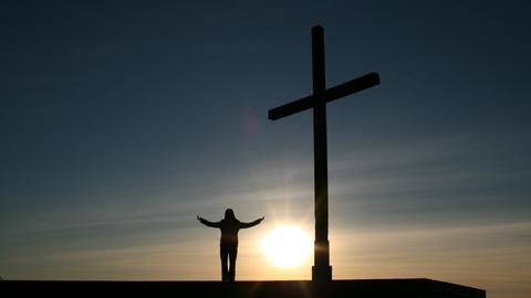 Person neben einem Kreuz im Sonnenuntergang