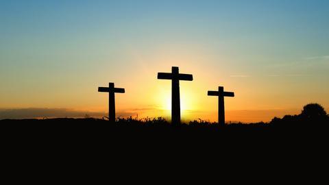 Drei leere Kreuze im Sonnenuntergang