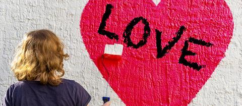 Eine Frau malt ein Herz an eine Wand