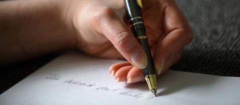 Linkshänder schreibt mit Kugelschreiber