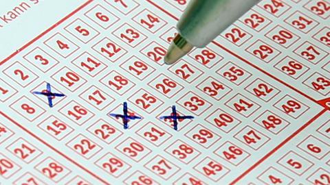 Jemand füllt einen Lotto-Schein aus und hat bisher die Zahlen 9, 24 und 32 angekreuzt