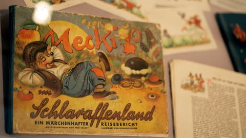 """Der Igel Mecki auf seinem ersten Buch """"Schlaraffenland"""""""