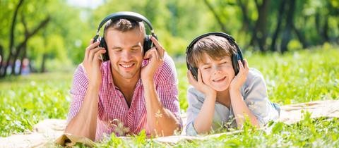 Ein Mann und ein Junge liegen im Grünen und hören Radio.