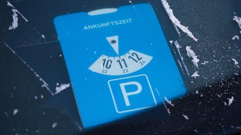 Parkscheibe vor einem Schild, das auf die Nutzung hinweist