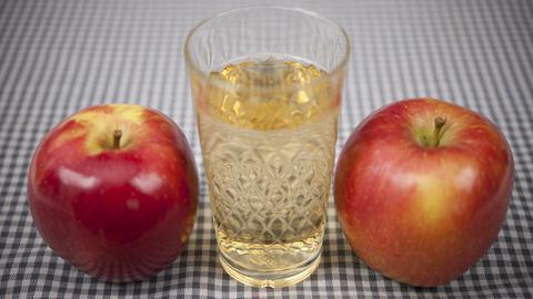 Ein Glas Apfelwein zwischen zwei Äpfeln