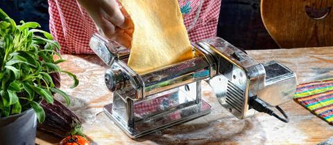 Flacher Teig wird in eine Nudelmaschine gezogen