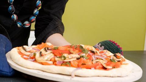 Junge Frau mit einer fertigen Pizza auf einem Pizzastein
