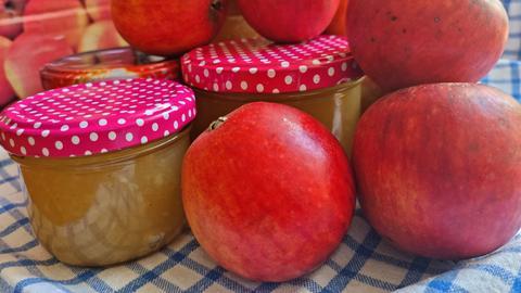 Apfelmarmelade im Glas, daneben liegen Äpfel
