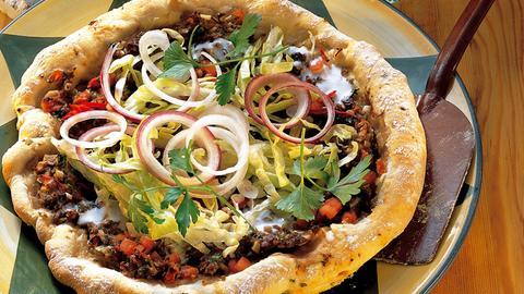 Eine türkische Pizza liegt auf einem Teller. Sie ist mit frischen Salat und Zwiebelringen belegt.