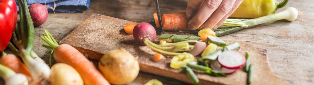 Blick auf Hände, die Gemüse schneiden
