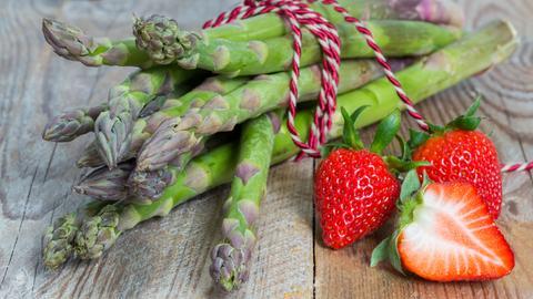 Grüner Spargel und Erdbeeren liegen auf einem Holzbrett