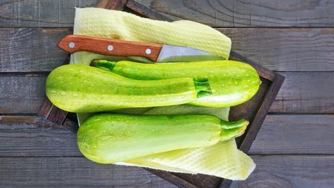 Zucchini liegen mit einem Messer auf dem Tisch