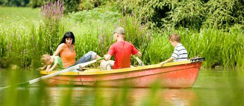 Familie rudert mit einem Boot auf einem See