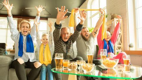 Eine Familie schaut Fußball im Fernsehen und jubelt.