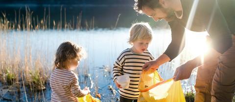 Vater sammelt mit zwei Kindern Müll