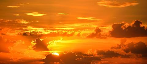 Himmel und Wolken erstrahlen in einem kräftigen Orange