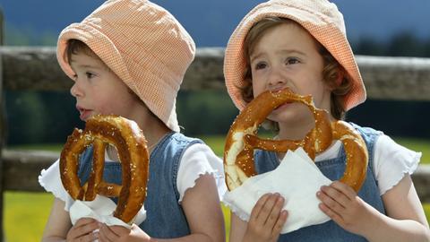 Zwei Kinder essen Brezel