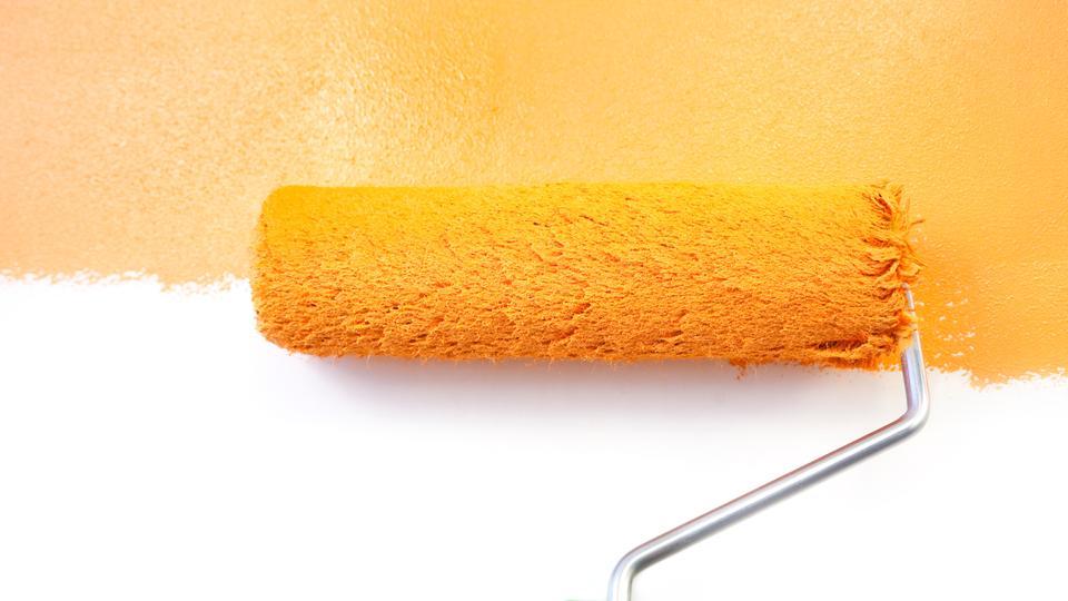 Weiße Wand wird mit oranger Farbe gewalzt