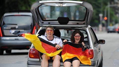 Zwei Fans sitzen mit Deutschland-Fahne im geöffneten Kofferraum eines fahrenden PKWs