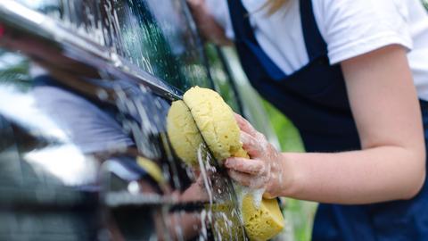 Eine Frau wäscht das Auto von außen