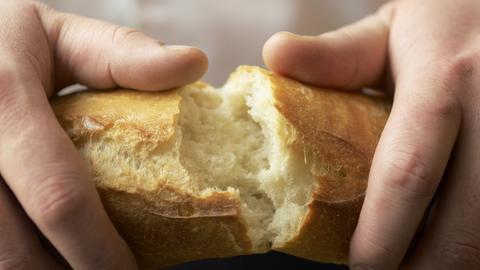Hände brechen ein Baguette auf