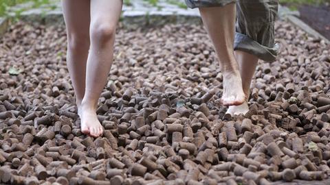 Zwei Personen laufen über Holzstückchen auf einem Barfußpfad