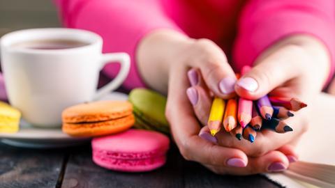 Eine Frau hält ein Bündel Buntstifte in den Händen. Neben ihr: eine Tasse und bunte Macarons.