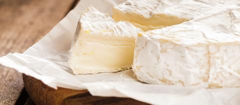 Ein frisch angeschnittenet Camembert liegt auf einem Käsebrett