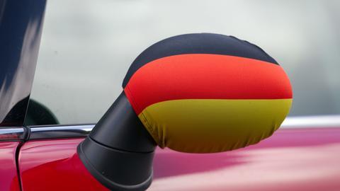 Schwarz-rot-goldener Stoffüberzug über einem Außenspiegel am Auto