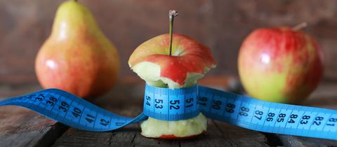 Symbolbild Diät: Ein Apfel mit einem Maßband