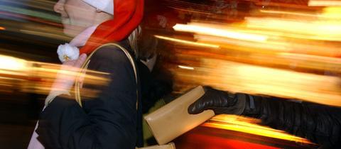Einer Weihnachtsmarktbesucherin wird das Portemonnaie aus der Tasche gezogen.