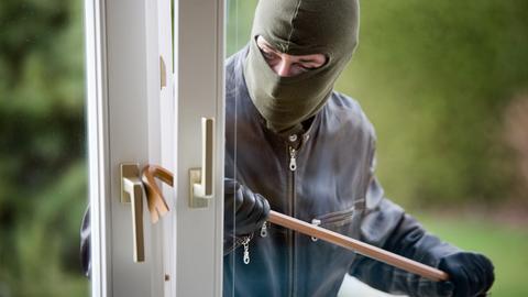 Ein Einbrecher macht sich am Fenster zu schaffen