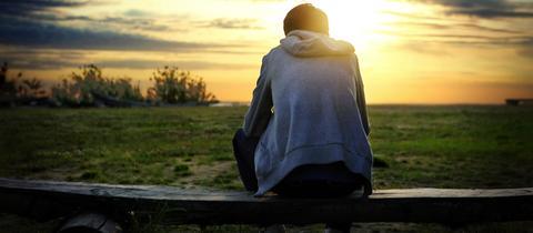 Ein Mann sitzt allein auf einer Bank