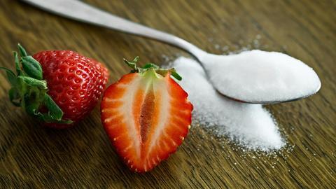 Erdbeeren und ein Löffel Zucker