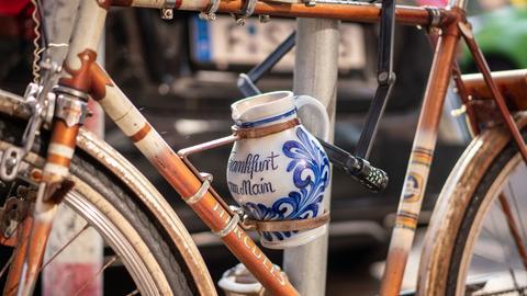 Ein Apfelwein-Bembel ist an einem Fahrrad befestigt.
