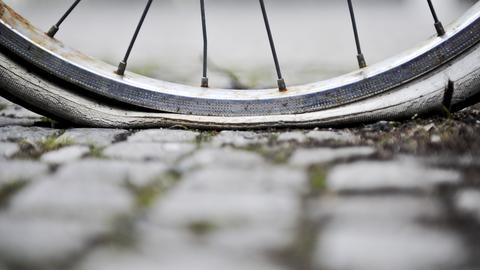 Platter Reifen eines Fahrrads auf Pflastersteinboden in Nahaufnahme.