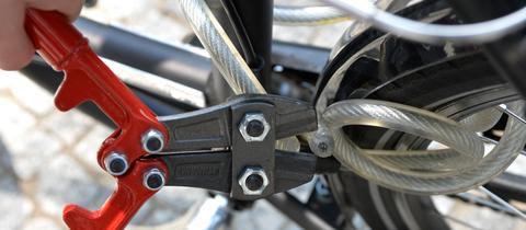 Ein Dieb mir Bolzenschneider und ein Fahrrad, dass mit einem Kabelschloss angeschlossen ist